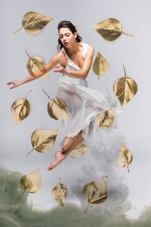 beautiful ballerina in white dress dancing surrounded by falling leaves near grey smoke on grey background