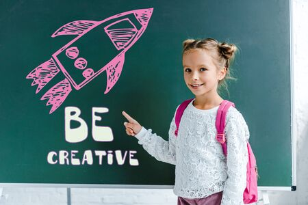 cheerful kid smiling while pointing with finger at be creativ lettering on green chalkboard Фото со стока
