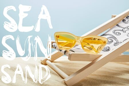 yellow stylish sunglasses on deck chair on sand and blue background with sea, sun, sand lettering