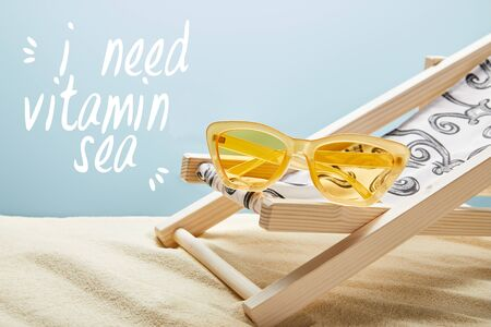 yellow stylish sunglasses on deck chair on sand on blue background with sun-kissed lettering Banco de Imagens