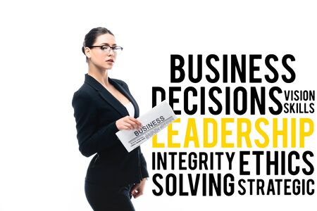confident businesswoman looking at camera and holding newspaper near business decisions, vision skills, leadership, integrity, ethics solving and strategic lettering isolated on white