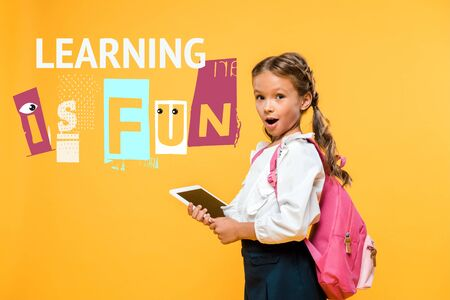 surprised schoolkid holding digital tablet with blank screen near learning in fun lettering on orange