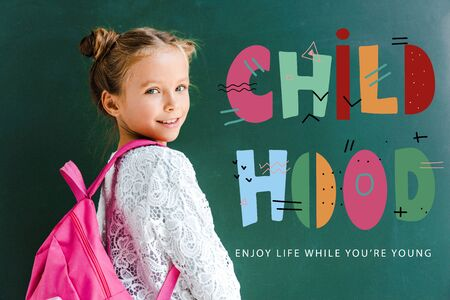 happy schoolkid smiling while standing with backpack near childhood lettering on green