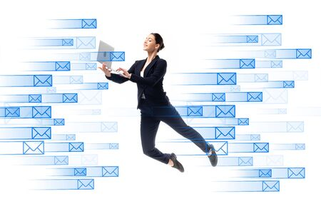 young businesswoman using laptop while levitating near e-mail icons isolated on white