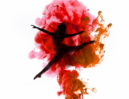 silhouette of ballerina dancing in colorful pink and red smoke splashes isolated on white Фото со стока