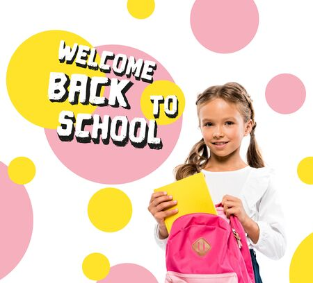 smiling child putting book in pink backpack near back to school lettering on white