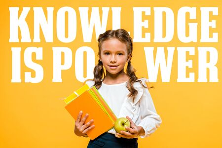 happy schoolchild holding tasty apple and books near knowledge is power lettering on orange Stock Photo