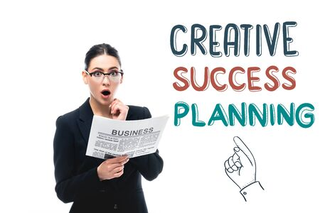 surprised businesswoman looking at camera while holding newspaper near creative success planning lettering and pointing hand isolated on white