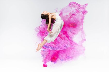 beautiful ballerina in white dress dancing in purple and pink paint splashes and spills on grey background