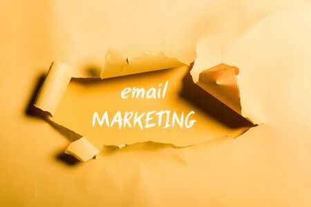 tattered paper with email marketing lettering and rolled edges on orange Фото со стока