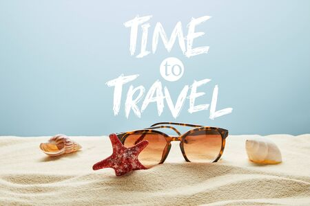 brown stylish sunglasses on sand with seashells and starfish on blue background with time to travel lettering