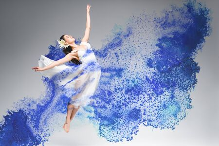 young ballerina in white dress dancing in blue paint splashes on grey background 版權商用圖片