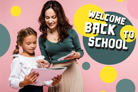 happy mother standing near cute daughter and welcome back to school lettering while painting on pink Фото со стока