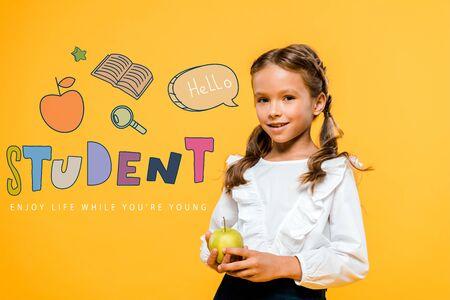 happy schoolchild holding tasty apple near student lettering on orange Фото со стока