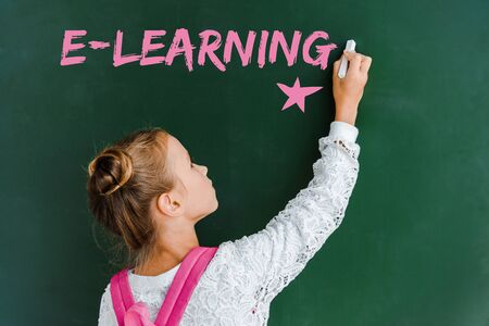 schoolchild holding chalk near chalkboard with e-learning lettering on green