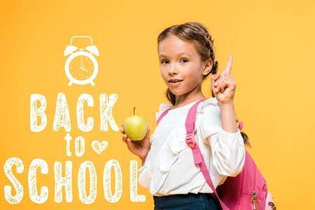 adorable schoolkid holding apple and pointing with finger near back to school lettering on orange