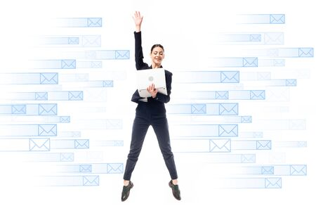 smiling businesswoman using laptop while jumping on background with e-mail icons isolated on white Stock fotó