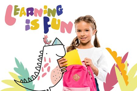 smiling child putting book in pink backpack near learning is fun lettering and fairy character on white