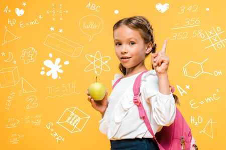 adorable schoolkid holding apple and pointing with finger near mathematical formulas on orange