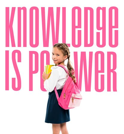 happy child holding books and standing with pink backpack near knowledge is power lettering on white Фото со стока
