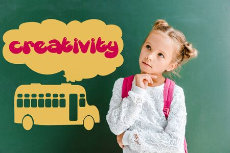 pensive kid standing with backpack near chalkboard with school bus and creativity lettering on green