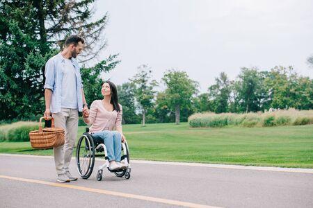 bel homme avec panier de paille tenant la main avec petite amie handicapée tout en marchant ensemble dans le parc Banque d'images