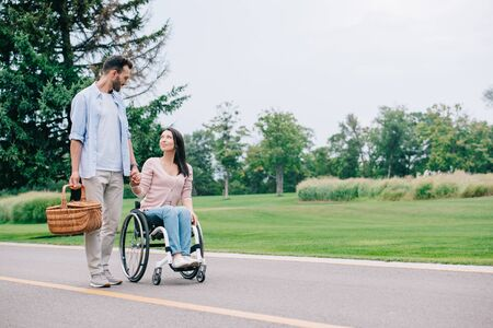 handsome man with straw basket holding hands with disabled girlfriend while walking in park together Reklamní fotografie