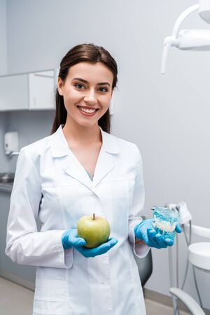 attractive and happy dentist holding teeth model and tasty apple in clinic 写真素材