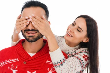 happy woman covering eyes of bearded man in sweater isolated on white