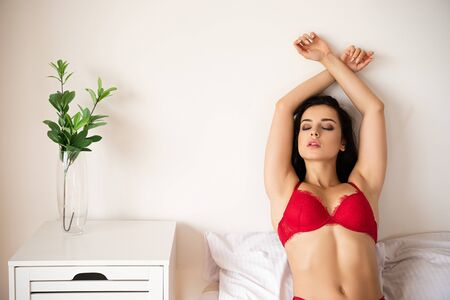 sexy girl in red bra relaxing while sitting in bed with closed eyes 版權商用圖片