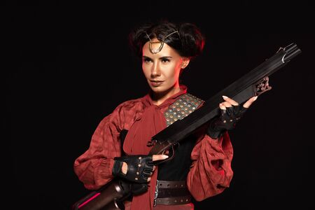 confident steampunk girl in leather gloves holding gun isolated on black