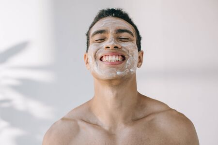 handsome mixed race man with cosmetic cream on face smiling with closed eyes