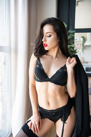 sexy girl in black underwear holding suit jacket while standing near window with closed eyes 版權商用圖片