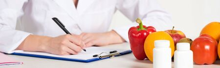 panoramic shot of dietitian in white coat writing in clipboard at workplace with pills, fruits and vegetables on table 免版税图像