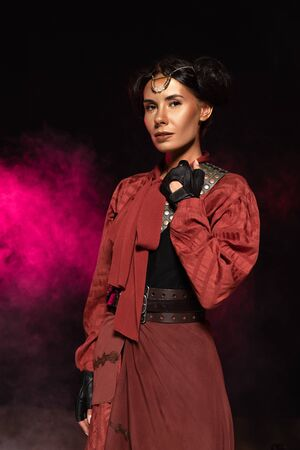 attractive steampunk woman looking at camera in smoke on black