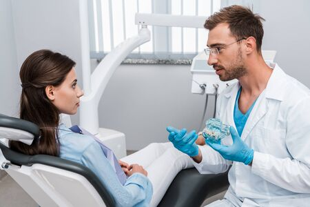selective focus of beautiful woman looking at handsome dentist in glasses holding tooth model