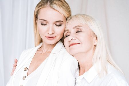 joyful blonde grandmother and granddaughter hugging in total white outfits with closed eyes 版權商用圖片 - 132007041