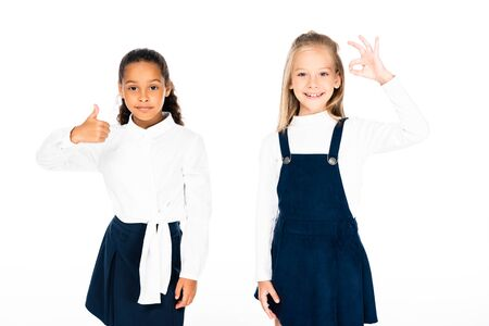 cute african american schoolgirl showing thumb up near multicultural friend showing ok gesture isolated on white