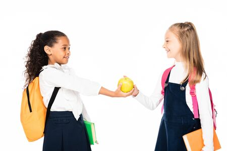 cheerful african american schoolgirl giving apple to friend isolated on white 写真素材 - 132007048