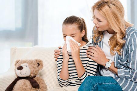 woman sitting near daughter sneezing in tissue near teddy bear