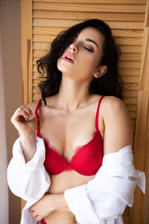 sexy girl in red underwear and white shirt leaning on wooden room divider and standing with closed eyes 版權商用圖片