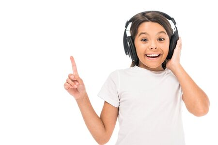 happy kid listening music in headphones and pointing with finger isolated on white Imagens