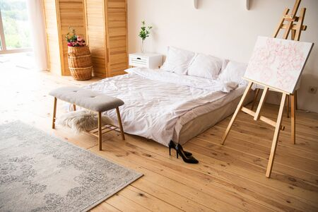 bedroom with white blanket and pillows, easel, bedside bench, carpet, room devider and black heels on wooden floor