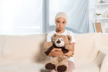 sick child sitting on sofa and holding teddy bear