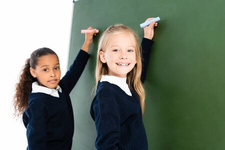 two smiling multicultural schoolgirls writing on chalkboard while looking at camera Archivio Fotografico