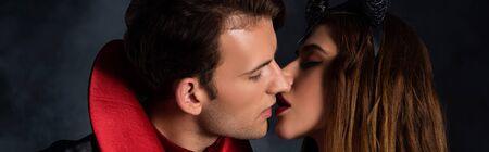 panoramic shot of man and pretty woman kissing on black 版權商用圖片