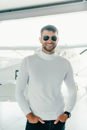 front view of smiling bearded man in sunglasses standing with hands in pockets near plane Banco de Imagens