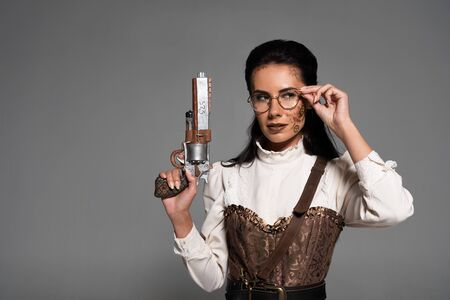 pensive steampunk woman holding vintage pistol and touching glasses isolated on grey