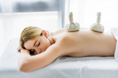 attractive woman lying on massage mat with herbal balls on back