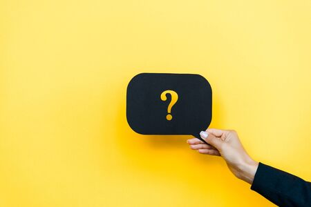 cropped view of woman holding black speech bubble with question mark on orange  스톡 콘텐츠